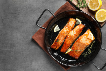 Dish with tasty cooked salmon on table, top view