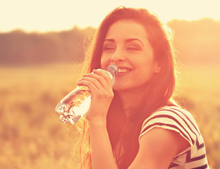 Happy smiling woman drinking water from the bottle on summer bright outdoor background. Closeup toned orange color portrait