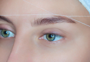 The make-up artist plucks her eyebrows with a thread close-up. Face care, beauty treatments in the beauty salon.