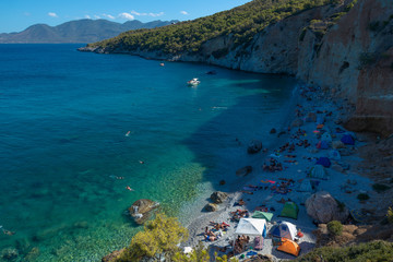 A sand beach with turqupoise waters and bathing guests