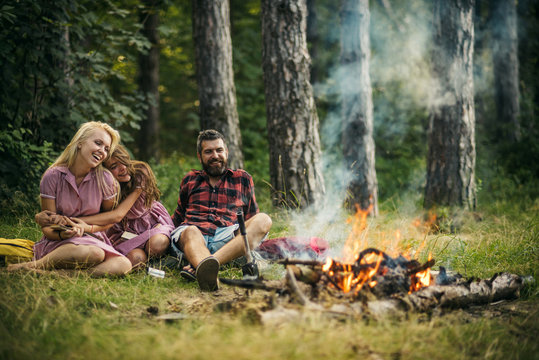 Young beautiful girls in retro dresses reading books in camp. Smiling brunette with curly hair hugging her blond sister while sitting next to bearded man. Friendship, family and leisure concepts