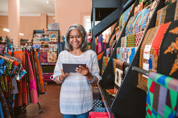 Smiling mature woman using a tablet in her textiles shop
