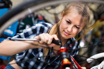 Woman is fixing wheel of bicycle in bicycle service