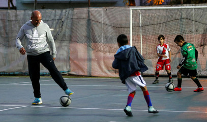 Uruguay's former soccer player Jose Batista kicks the ball, as he teaches soccer to kids, at a club where he works before an interview with Reuters in Buenos Aires