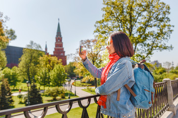 Mixed race woman tourist taking pictures on mobile phone on the backgroung the Kremlin wall tower. Travel to Russia concept