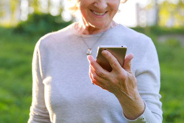 Elderly woman is holding a phone in a sunny park. Show care and love for the elderly, help charitable foundations