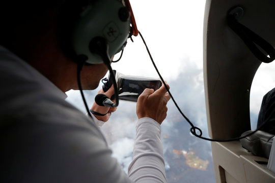 Sightseer Josh Gavrilov takes pictures of the lava zone while flying in a helicopter over the Leilani Estates near Pahoa, Hawaii