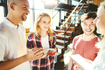 Group of four diverse college students having fun while discussing project together