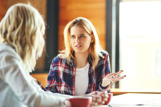 Two young female friends chatting over coffee in cafe. Blonde women discussing issues