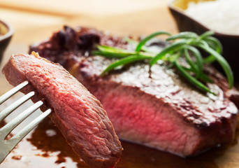 grilled and sliced steak with one slice on fork on wooden background