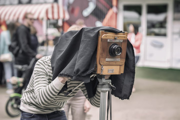 Photographer with vintage wooden camera under dark cloth cape, photographing clients, artifact, antiquity, rarity concept