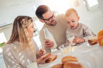 Happy young family having breakfast