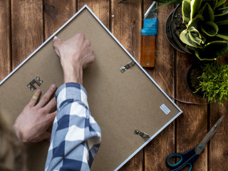 overhead man putting a photo in a wooden frame
