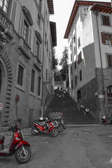Artistic black and white photo of a narrow street with red motorbikes and steps at background. Selective color effect. Florence, Italy.