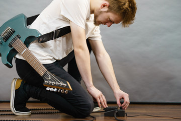 Man adjusting guitar effects pedal
