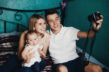 Daddy taking pictures of his family. Young man making selfie with his wife and little daughter. Modern parents, child, blogging, photography, childhood, parenthood, family bonds, marriage concept