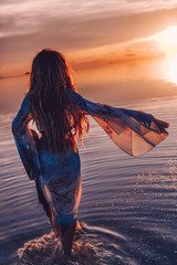 beautiful young woman in elegan dress walking on water at sunset
