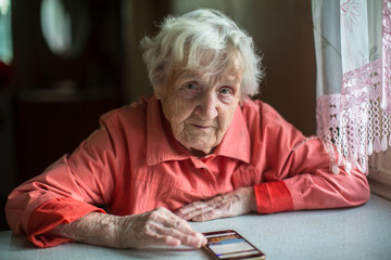 Elderly woman sits with a smartphone.