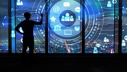 Social Media with man writing on large windows high above a sprawling city at night