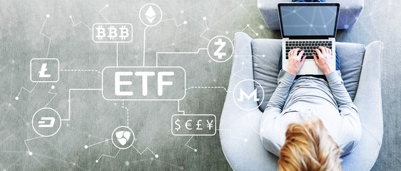 Cryptocurrency ETF theme with man using a laptop in a modern gray chair