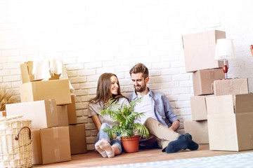 Charming happy couple embracing in love sitting with flowerpot and carton boxes on floor.