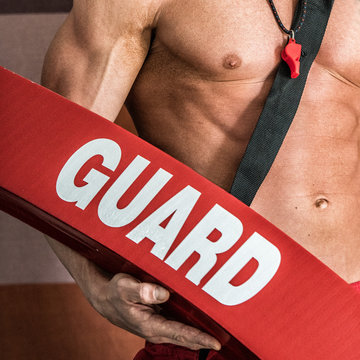 Professional lifeguard with sexy strong body holding red safety tube and whistle