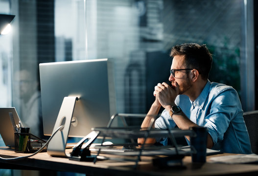 Formal man sitting at desk in office spending overtime hours at work looking tiredly away.