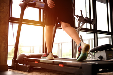 woman  running on the machine treadmill at fitness gym