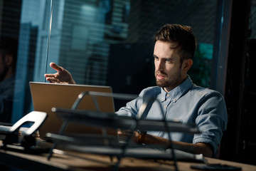 Misunderstanding man sitting and pointing at laptop in office at night.