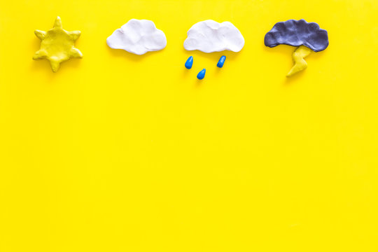 Weather forecast concept. Modern weather icons set on yellow background top view copy space