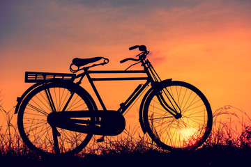 beautiful landscape image with Silhouette  Bicycle at sunset in vintage tone style