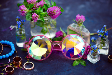 Fotobehang Carnaval Stylish pink kaleidoscopic sunglasses with golden bracelets and rings in a feminine style concept with clover flowers on a dark background. Beautiful summer accessories.