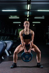 Strong, muscular, girl in black shorts, doing a squat with a pancake from the bar, legs wide apart. Dark gym.
