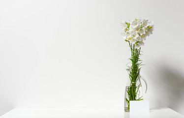 bellflower in a vase on a table by the wall and blank sheet for text, white background