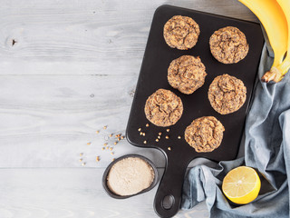 Healthy gluten-free homemmade banana muffins with buckwheat flour. Vegan muffins with poppy seeds on black cutting board over gray wooden table. Copy space. Top view or flat lay.