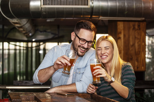 Young couple looking each other in local pub with glass of beer