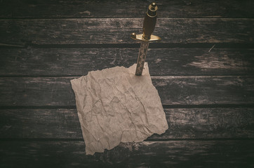 Crumpled brown paper page parchment and the dagger blade thrust in a table. Adventurer treasure hunter or pirate concept background.