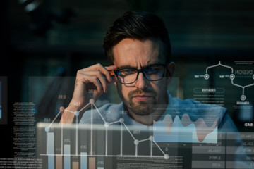 Man in eyeglasses watching monitor of computer sitting alone late at night in office having overhours. Wall mural