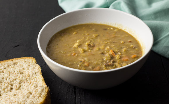 Soup and bread on rustic black table