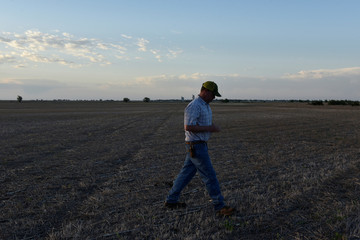 Farmer Drew Malchoff walks through a field that will be planted with cotton near Wakita, Oklahoma