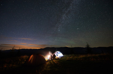 Back view of mother and two children tourists having a rest at night camping in mountains, sitting on log beside campfire and glowing tent, looking at beautiful starry sky and Milky way in evening