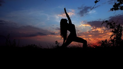 Woman doing yoga, female silhouette in evening sky background. Concept of asanas and relaxing before night.