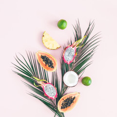 Summer fruits. Tropical palm leaves, pineapple, coconut, papaya, dragon fruit, orange on pastel pink background. Flat lay, top view, square