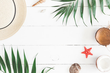 Summer composition. Tropical palm leaves, hat, pineapple, coconut on white wooden background. Summer concept. Flat lay, top view, copy space