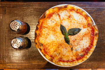 Top view of Margarita pizza topping with basil leaves served with oregano and chili powder.