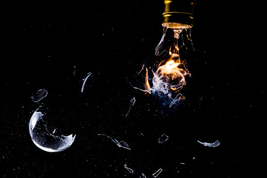 A shattering Lit Lightbulb.  A light bulb shattering while lit, with flame and smoke and stop action on shattering glass