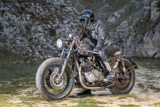 Biker with black leather suit and mask stay on his custom special rat motorbike.  Desolated rocks in the background. Post apocalyptic concept