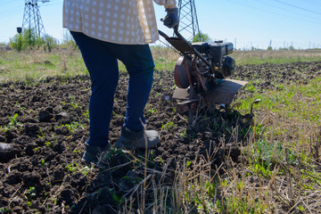 fermer plows the land with a motor-block