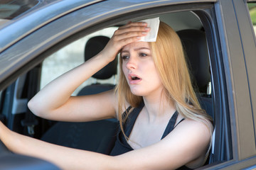 Woman being hot during a heat wave in car