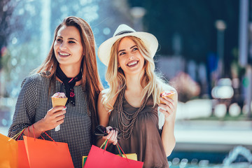 Happy young women with shopping bags and ice cream having fun on city street